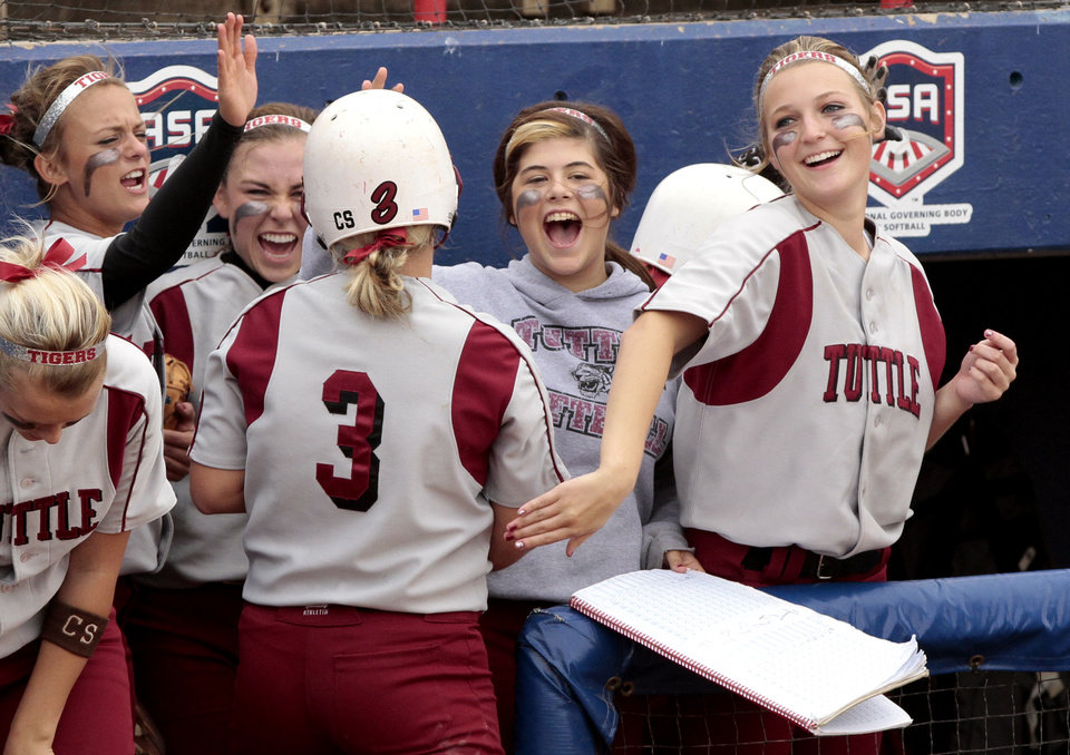 Photo - Tuttle players celebrate a score from Annie Combs (3) in the first round at the 2012 State Fast-Pitch Softball Tournament on Thursday, Oct. 11, 2012 at ASA Hall of Stadium in Oklahoma City, Okla.  Photo by Steve Sisney, The Oklahoman