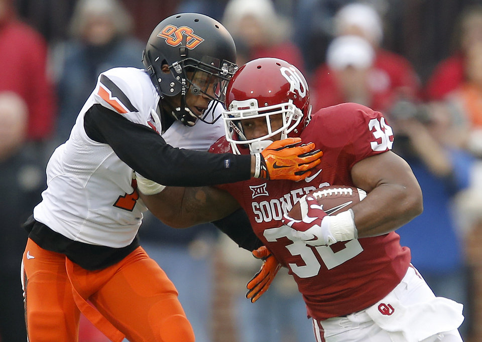 Photo - Oklahoma's Samaje Perine (32) fights off Oklahoma State's Kevin Peterson (1) during a Bedlam college football game between the University of Oklahoma Sooners (OU) and the Oklahoma State Cowboys (OSU) at Gaylord Family-Oklahoma Memorial Stadium in Norman, Okla., Saturday, Dec. 6, 2014. Photo by Bryan Terry, The Oklahoman