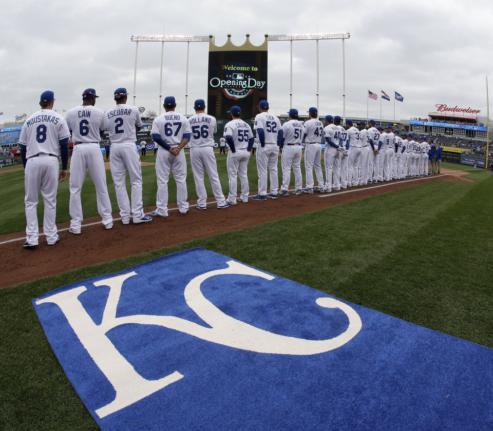 Photo - Players for the Kansas City Royals stand for the national anthem before a home opener baseball game against the Chicago White Sox Friday, April 4, 2014, in Kansas City, Mo. (AP Photo/Charlie Riedel)