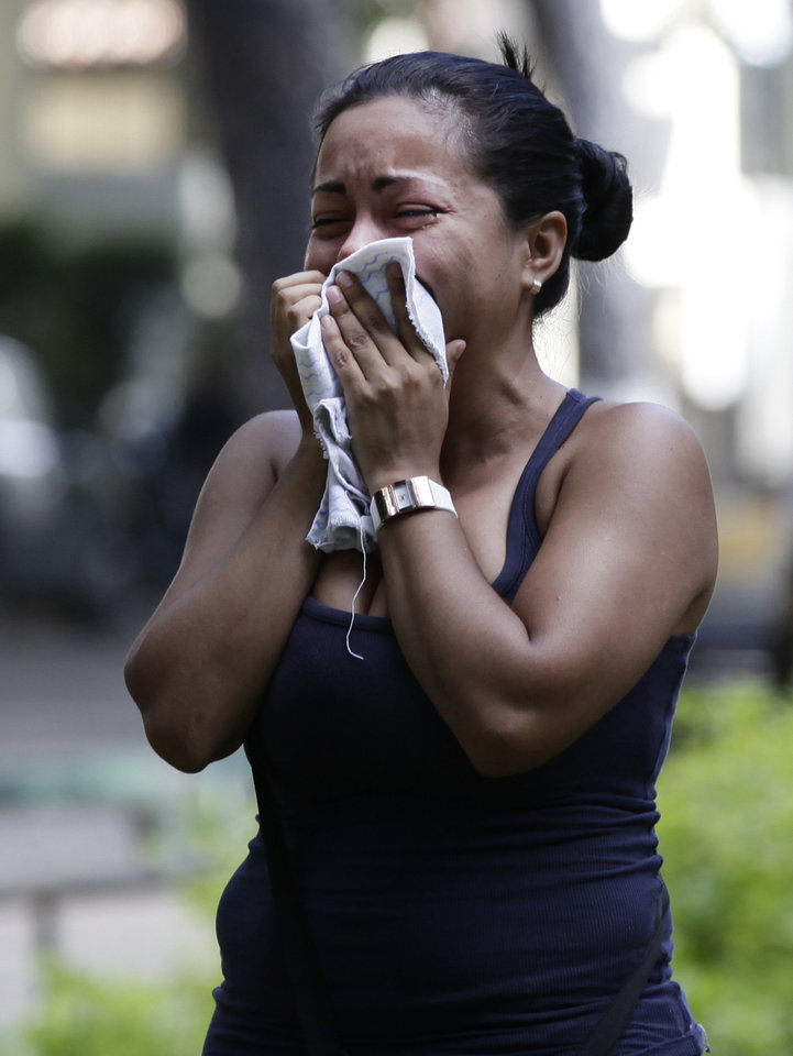 Photo -   A relative of an inmate taking part of a protest against measures taken by authorities to control a riot at the La Planta prison cries during clashes with National Guard soldiers outside the jail in Caracas, Venezuela, Thursday, May 17, 2012. Gunfire erupted on Thursday inside the prison where armed inmates have prevented security forces from retaking control for nearly three weeks. (AP Photo/Ariana Cubillos)