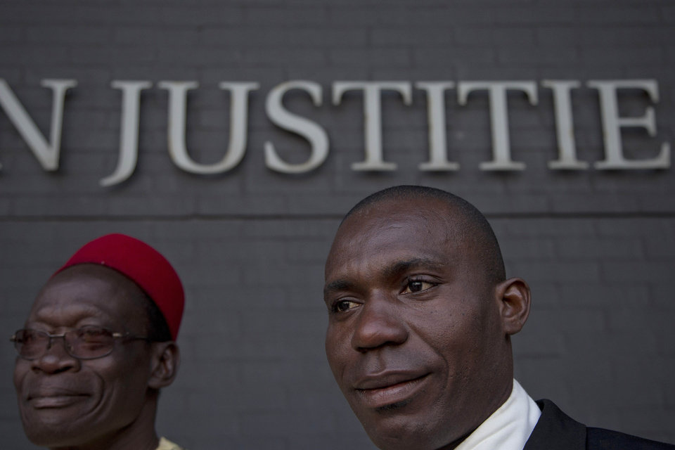 Alali Efanga, right, and Chief Fidelis A. Oguru, plaintiffs in the court case of Nigerian farmers against Shell, wait for the start of their case in The Hague, Netherlands, Thursday Oct. 11, 2012. Nigerian farmers are suing Shell in a Dutch court, asking judges to order the oil multinational to clean up environmental damage the farmers say is caused by leaking pipes. Thursday\'s case in The Hague Civil Court is a legal landmark in the Netherlands as it marks the first time a Dutch company has been sued for alleged environmental mismanagement caused by an overseas subsidiary. (AP Photo/Peter Dejong)