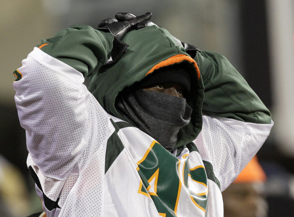 Photo -   A bundled up Miami Hurricane fan looks downfield during the second half of an NCAA college football game against Notre Dame at Soldier Field, Saturday, Oct. 6, 2012, in Chicago. (AP Photo/Nam Y. Huh)