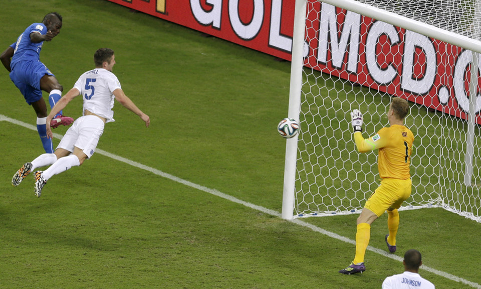 Photo - Italy's Mario Balotelli, left, scores his side's 2nd goal past England's goalkeeper Joe Hart, right, during the group D World Cup soccer match between England and Italy at the Arena da Amazonia in Manaus, Brazil, Saturday, June 14, 2014.  (AP Photo/Themba Hadebe)
