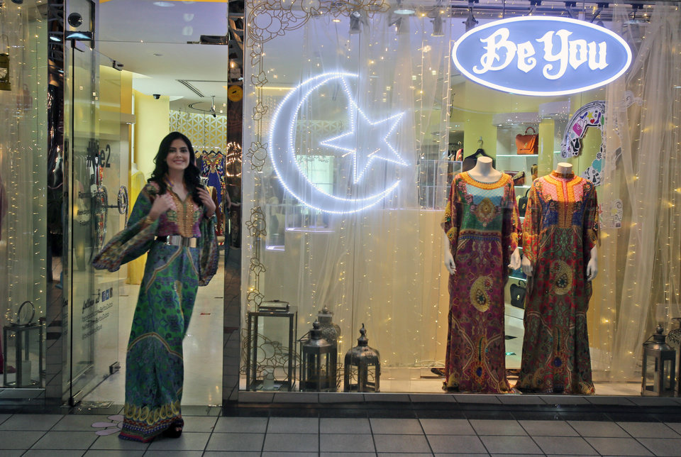 Photo - In this Tuesday, July 14, 2014 photo, fashion designer Tamara Al Gabbani walks out of the Be You boutique, which is decorated with the Islamic crescent symbol representing the season of Ramadan, in one of her designs from the Jalabiya collection in Dubai, United Arab Emirates. Ramadan, Islam's holiest month, is a boon for retailers in the Middle East, South Asia and beyond. And while some Muslims welcome it as a positive sign, others see it as commercialization of a sacred time of year, threatening to subvert its very nature. (AP Photo/Kamran Jebreili)