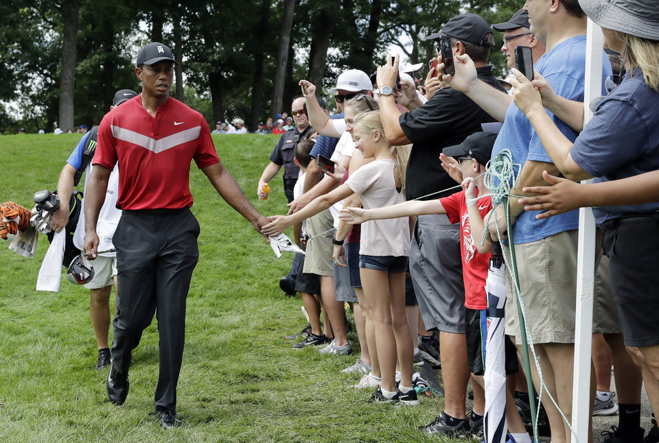 Photo -  Tiger Woods, left, greets fans as he walks to the 14th fairway after hitting his tee shot during the final round of the BMW Championship golf tournament at Medinah Country Club, Sunday, Aug. 18, 2019, in Medinah, Ill. (AP Photo/Nam Y. Huh)