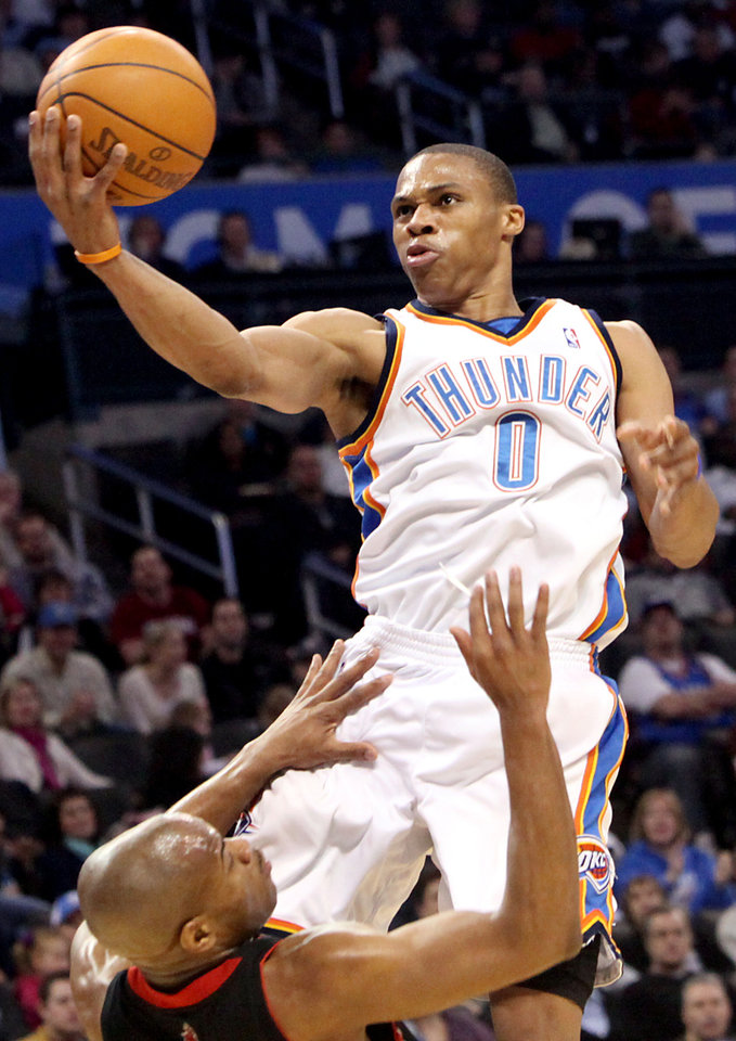 Photo - Oklahoma City's Russell Westbrook puts up a shot over Toronto's Jarrett Jack  during their NBA basketball game at the Ford Center in Oklahoma City on Sunday, Feb. 28, 2010. The Thunder beat the Raptors 119-99. Photo by John Clanton, The Oklahoman