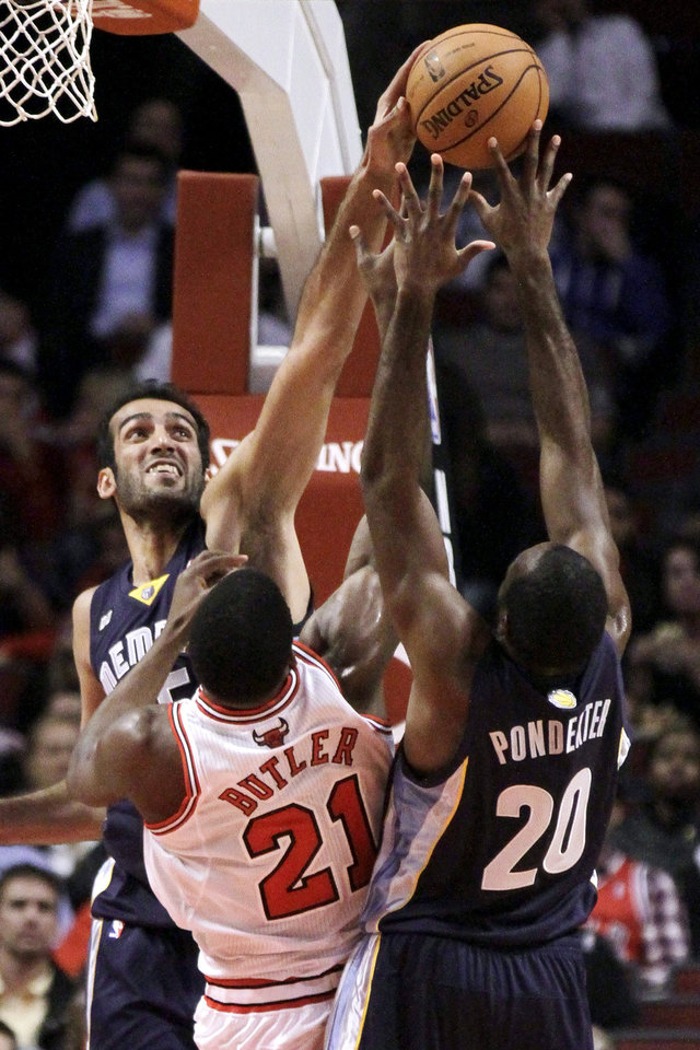Photo -   Memphis Grizzlies center Hamed Haddadi, left, blocks the shot of Chicago Bulls guard Jimmy Butler (21) as Grizzlies' Quincy Pondexter (20) defends during the first half of a preseason NBA basketball game, Tuesday, Oct. 9, 2012, in Chicago. (AP Photo/Charles Rex Arbogast)
