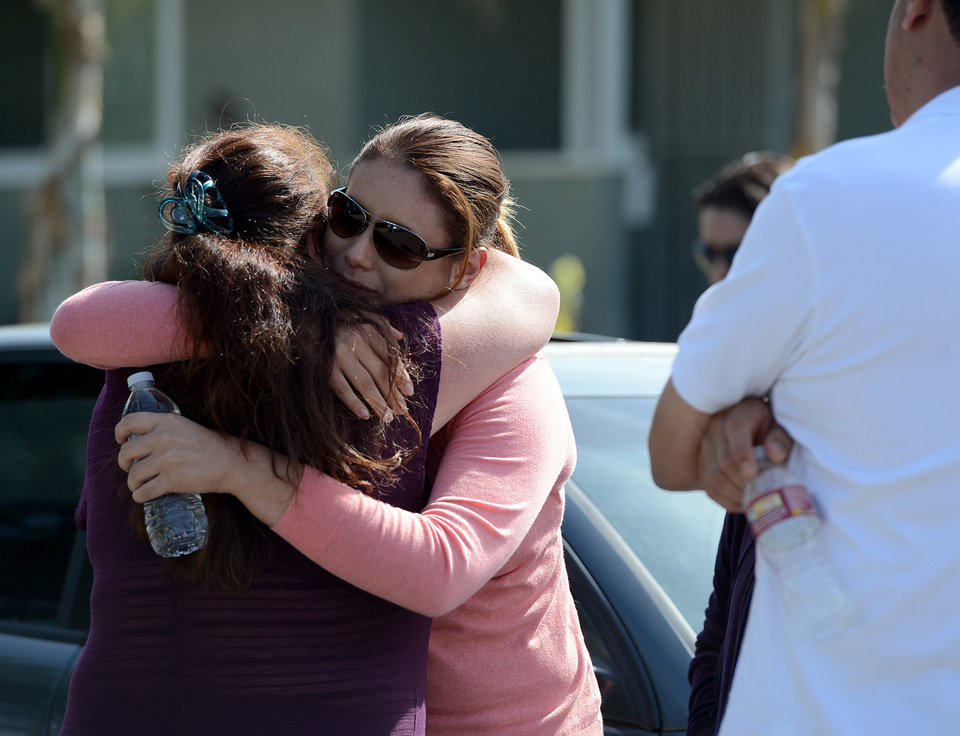 Photo - April Mejia, right, is comforted at the scene as Pomona Police investigate the scene of a murder-suicide in Pomona, Calif., on Friday, May 9, 2014.  A 28-year-old man shot and killed three members of a Southern California family at the home where they all lived before turning the gun on himself, authorities said Friday. The four bodies were found late Thursday inside the single-story house in a residential area of Pomona, police Lt. Michael Keltner said at a morning news conference.  A woman in her 50s and her 24-year-old daughter and 17-year-old son were killed in their respective bedrooms, he said. (AP Photo/The Inland Valley Daily Bulletin, Jennifer Cappuccio Maher)  MANDATORY CREDIT