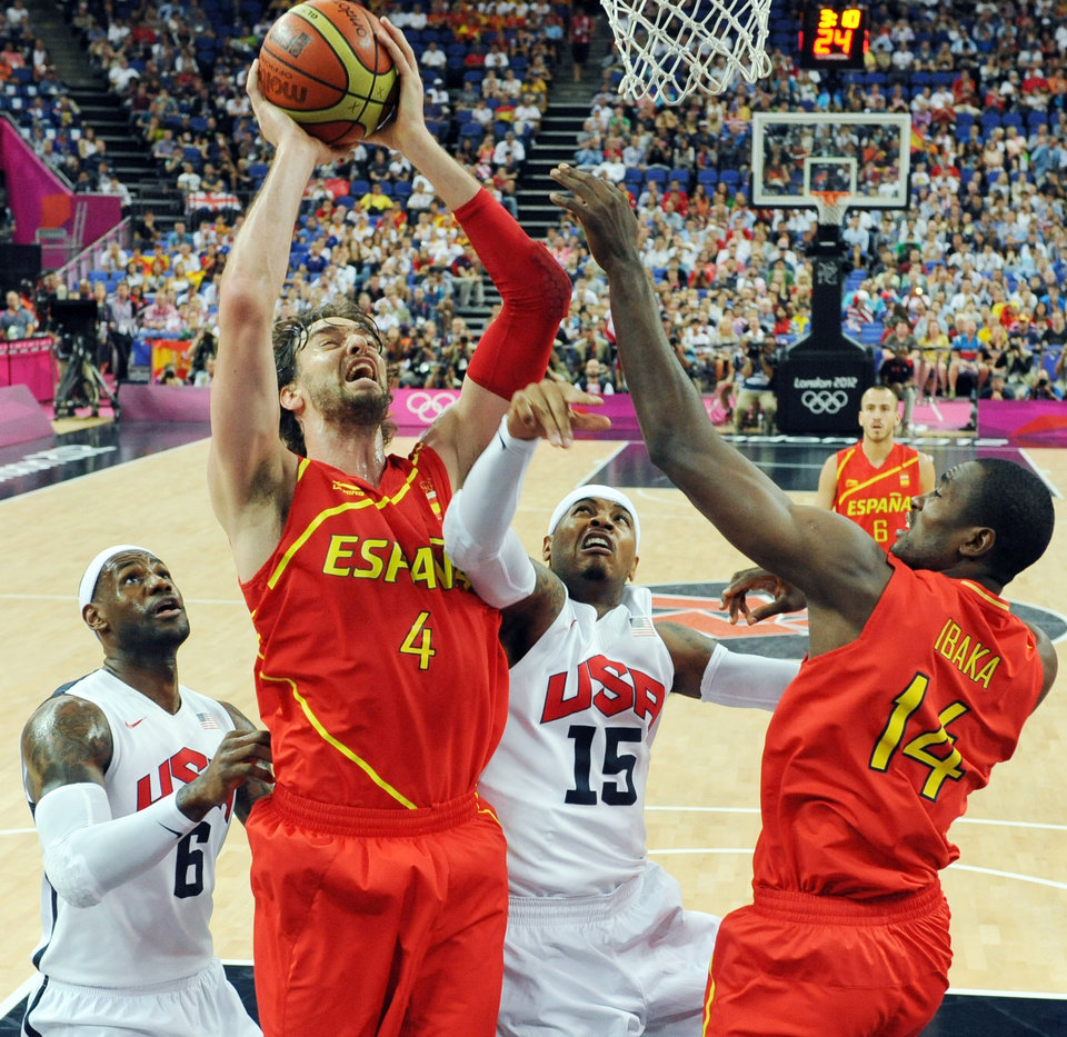 Spain\'s Pau Gasol (4) jumps to score over United States\' LeBron James (6) and Carmelo Anthony (15) during the men\'s gold medal basketball game at the 2012 Summer Olympics in London on Sunday, Aug. 12, 2012. (AP Photo/Mark Ralston, Pool)