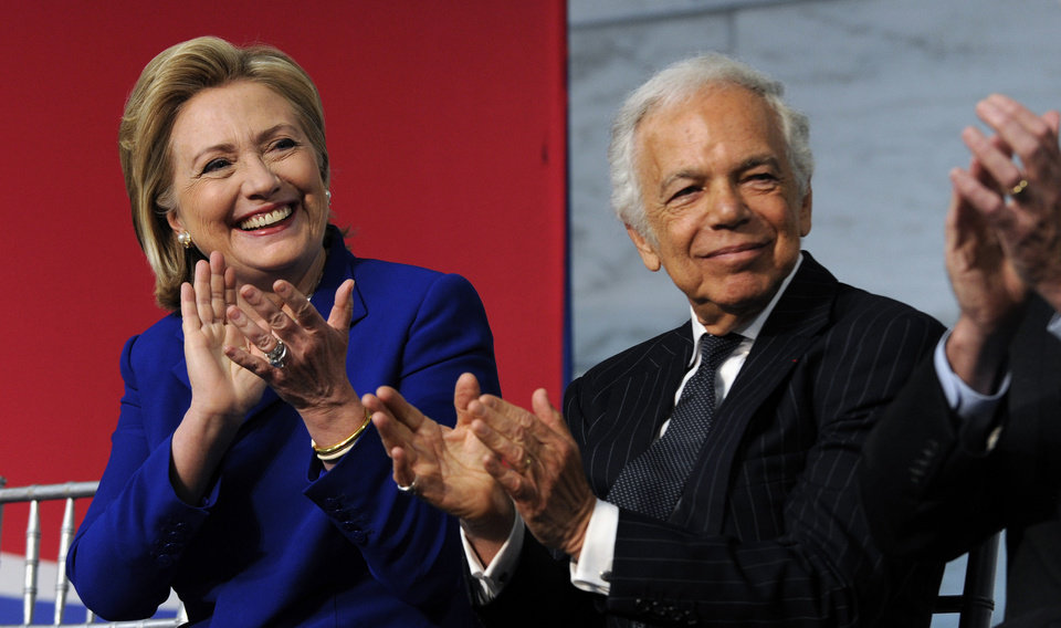 Photo - Designer Ralph Lauren and former Secretary of State Hillary Clinton applaud a group of newly sworn-in citizens during a naturalization ceremony at the Smithsonian's National Museum of American History in Washington, Tuesday, June 17, 2014. Lauren was also honored for his efforts to fund the conservation of the flag that inspired the national anthem. (AP Photo/Susan Walsh)