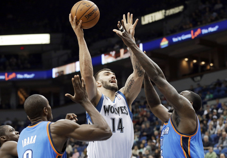 Minnesota Timberwolves\' Nikola Pekovic, center, of Montenegro, shoots between Oklahoma City Thunder\'s Serge Ibaka, left, and Kendrick Perkins in the first quarter of an NBA basketball game, Friday, Nov. 1, 2013, in Minneapolis. (AP Photo/Jim Mone)