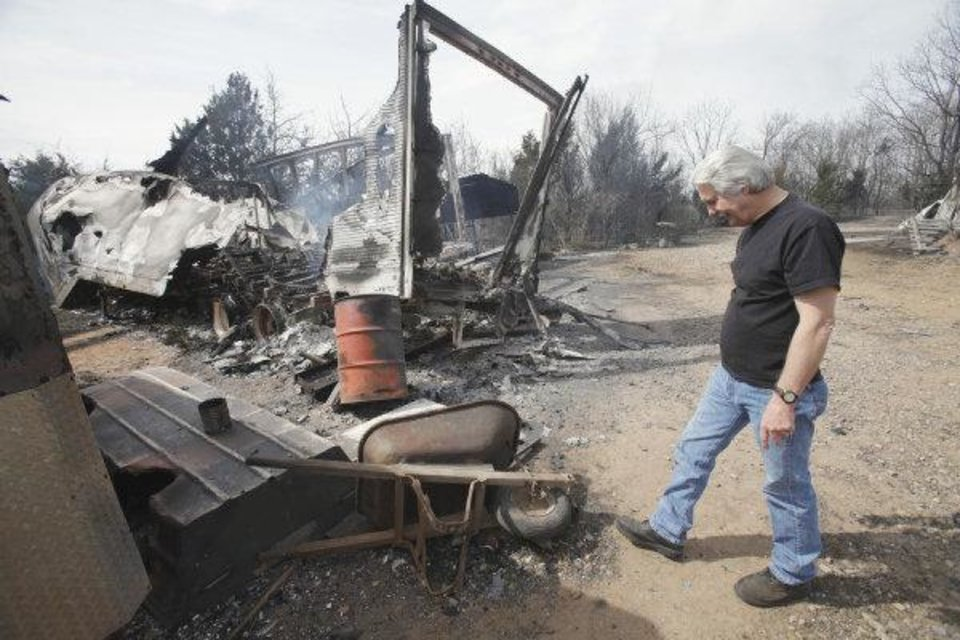 Photo - Tom Anglin surveys a burned trailer, recreational vehicle, and outbuildings on his property soug of State Highway 9 on Saturday, March 12, 2011, in Goldsby, Okla. in the aftermath of Friday's grass fire  Photo by Steve Sisney, The Oklahoman ORG XMIT: KOD  STEVE SISNEY - THE OKLAHOMAN