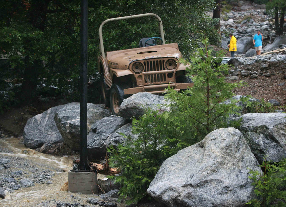 Photo - In this Sunday, Aug. 3, 2014 photo, a jeep sits perched atop a boulders at Forest Home Christian Conference Center in Forest Falls, Calif. following a rock and mudslide. Crews on Monday have cleared several feet of mud, rocks and debris that had blocked San Bernardino County roads, stranding some 2,500 people in the rural communities of Oak Glen and Forest Falls. (AP Photo/The Press-Enterprise, David Bauman)  MAGS OUT; MANDATORY CREDIT