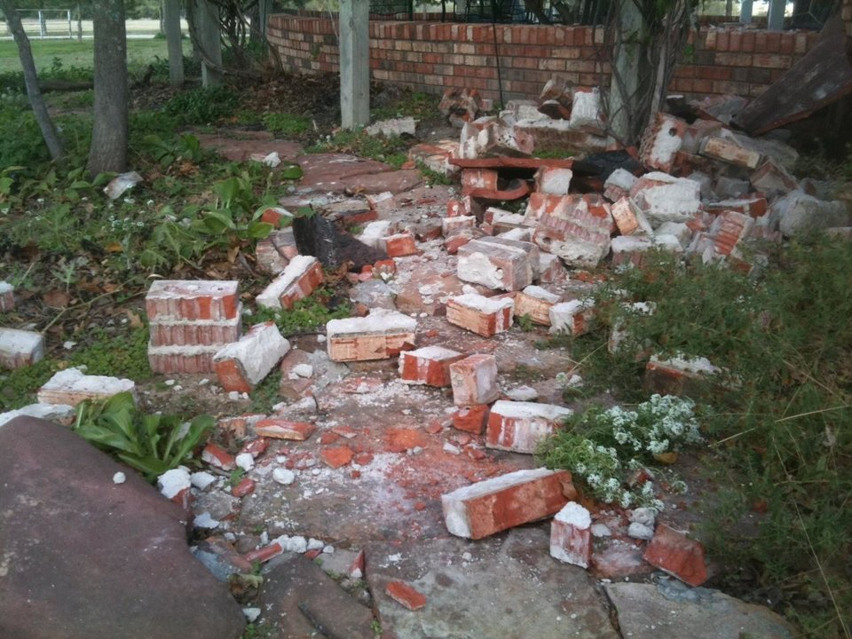 Photo - Bricks from chimney fell to the ground on back side of home of Joseph and Mary Reneau in Lincoln County. The quake heavily damaged their home near Sparks, OK .
