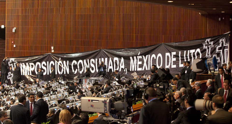 Photo - Members of the National Congress hang a giant protest banner that reads in Spanish: