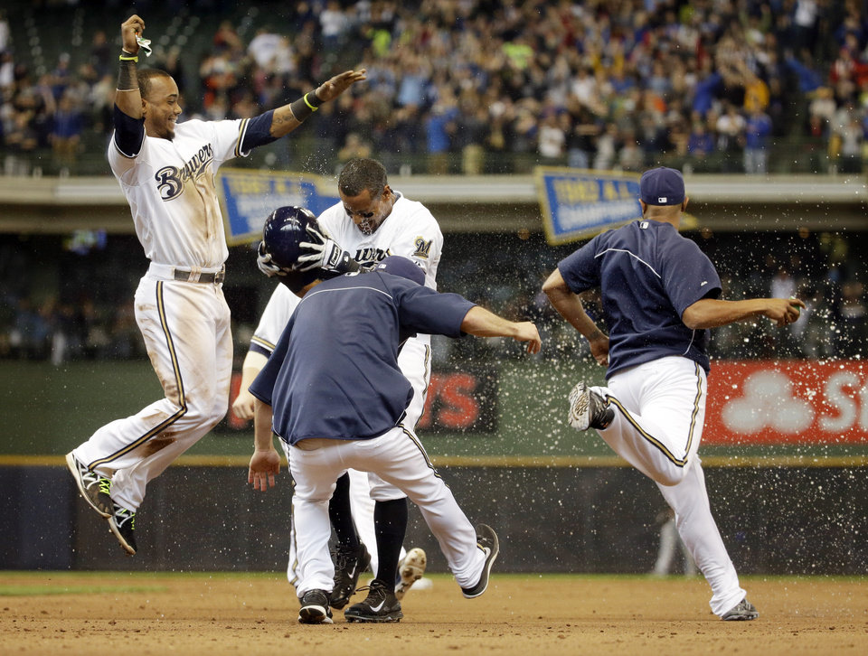 Photo - Milwaukee Brewers' Khris Davis is mobbed by teammates after hitting a walk-off two-run single during the ninth inning of a baseball game against the Pittsburgh Pirates Thursday, May 15, 2014, in Milwaukee. The Brewers won 4-3. (AP Photo/Morry Gash)