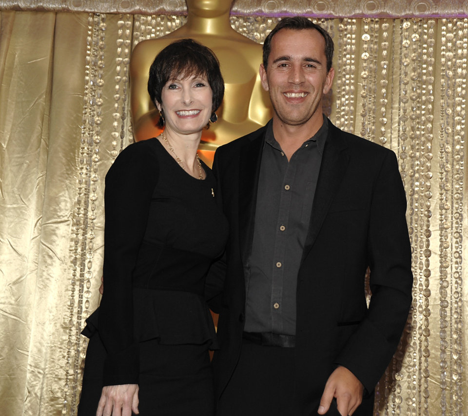 Photo - Producer Gale Anne Hurd, left, and director Nikolaj Arcel pose together during the The Oscars Foreign Language Film Award Directors Reception at The Academy of Motion Picture Arts and Sciences in Beverly Hills, Calif. on Friday, Feb. 22, 2013. Arcel's feature film