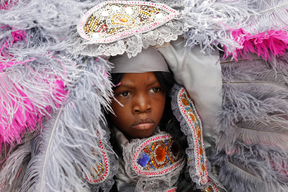 A Spy Boy with the Cheyenne Mardi Gras Indian tribe parades with the tribe at the New Orleans Jazz and Heritage Festival in New Orleans, Thursday, May 3, 2012. (AP Photo/Gerald Herbert)