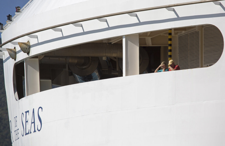 Photo - Passengers look out from the Royal Caribbean International's Explorer of the Seas, docked at Charlotte Amalie Harbor in St. Thomas, U. S. Virgin Islands, Sunday, Jan. 26, 2014. U.S. health officials have boarded the cruise ship to investigate an illness outbreak that has stricken at least 300 people with gastrointestinal symptoms including vomiting and diarrhea. (AP Photo/Thomas Layer)