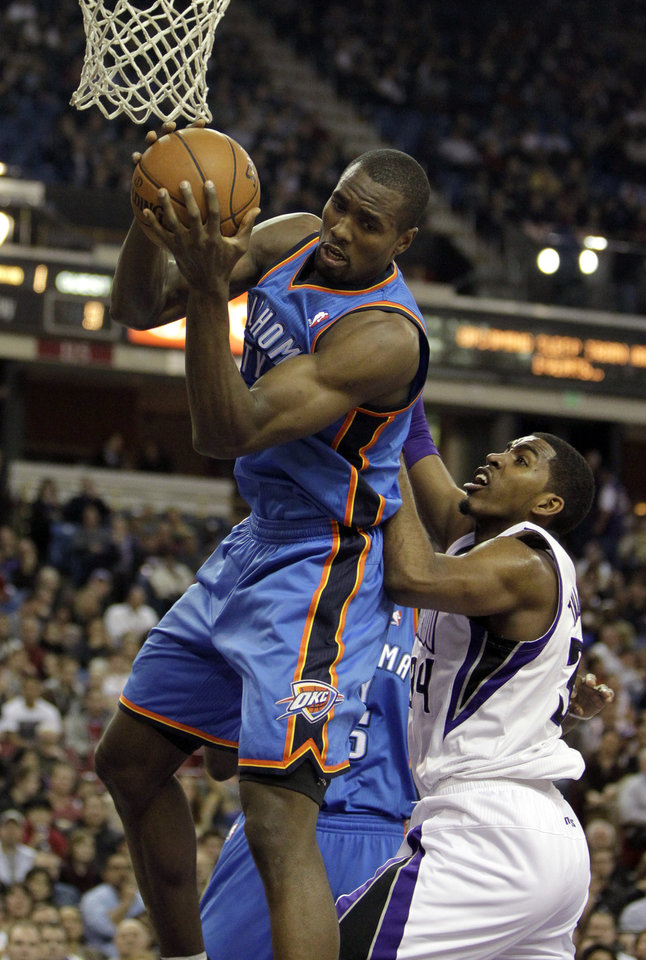 Oklahoma City Thunder center Serge Ibaka, top, of the Republic of Congo, left, grabs a rebound against Sacramento Kings forward Jason Thompson during the first quarter of  an NBA basketball game in Sacramento, Calif., Friday, Jan. 25, 2013. (AP Photo/Rich Pedroncelli) ORG XMIT: SCA103