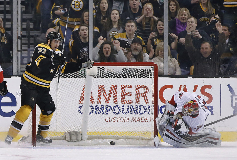 Photo - Boston Bruins center Patrice Bergeron (37) celebrates after scoring against Ottawa Senators goalie Craig Anderson (41) during the first period of an NHL hockey game in Boston, Saturday, Feb. 8, 2014. (AP Photo/Elise Amendola)