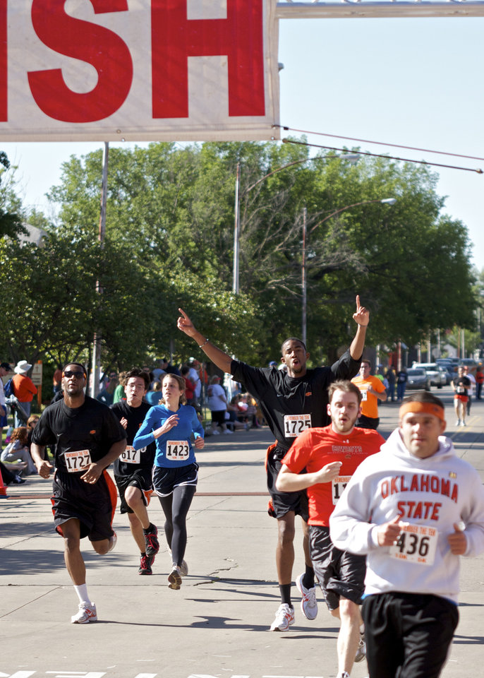 OSU basketball team member, Michael Cobbins, holds his hands up as he crosses the finish line of the Remember the Ten run was  in Stillwater, Okla on April 21, 2012. Photos by Mitchell Alcala for The Oklahoman  ORG XMIT: KOD
