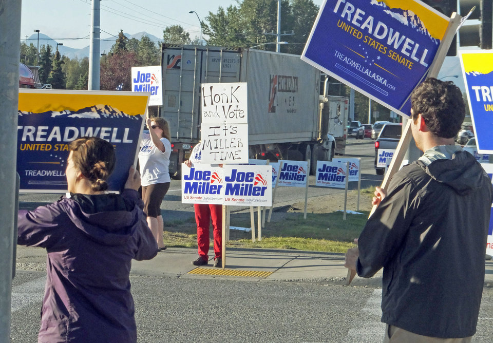 Photo - Supporters of the major U.S. Senate candidates wave signs on the morning of Alaska's primary election Tuesday, Aug. 19, 2014, in Anchorage. Here, supporters for two of the GOP Senate candidates, Mead Treadwell and Joe Miller, stand across an intersection from one another. The other major Republican candidate is Dan Sullivan, who was out with supporters on a different street. (AP Photo/Becky Bohrer)
