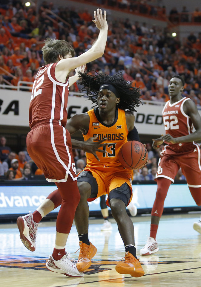 Photo - Oklahoma State's Isaac Likekele (13) tries to get past Oklahoma's Austin Reaves (12) during an NCAA men's Bedlam basketball game between the Oklahoma State University Cowboys (OSU) and the University of Oklahoma Sooners (OU) at Gallagher-Iba Arena in Stillwater, Okla., Saturday, Feb. 22, 2020. Oklahoma State won 83-66. [Bryan Terry/The Oklahoman]