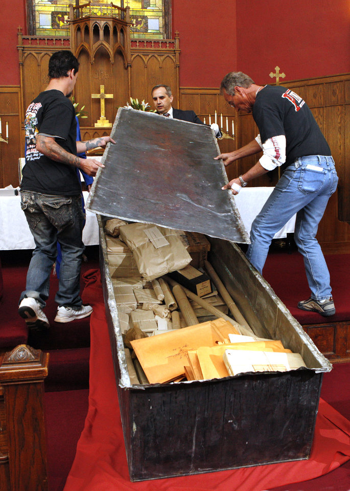 Chad Williams, center, Oklahoma History Center research division director, and workers remove the lid of the Century Chest at First Lutheran Church in Oklahoma City Monday, April 22, 2013. The Century Chest is a time capsule put together and buried April 22, 1913 by the church. Photo by Paul B. Southerland, The Oklahoman