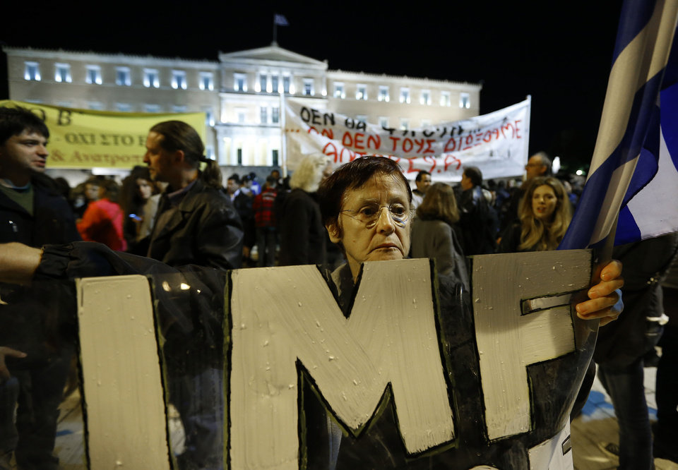 Photo -   A woman holds an IMF banner in front of the Parliament in Athens on Sunday Nov. 11, 2012. Hundreds of protesters were converging on the Greek capital's main square outside Parliament on Sunday evening, as lawmakers debated the 2013 budget, which includes pension and salary cuts demanded by the country's international creditors in order for them to approve the next vital batch of rescue loans. Lawmakers were to vote at midnight or shortly after, and the legislation is expected to pass. The vote comes four days after a separate bill of deep spending cuts and tax hikes for 2013-14 squeaked past with a narrow majority in the 300-member Parliament following deep disagreements among the members of Greece's three-party coalition government.(AP Photo/Lefteris Pitarakis)
