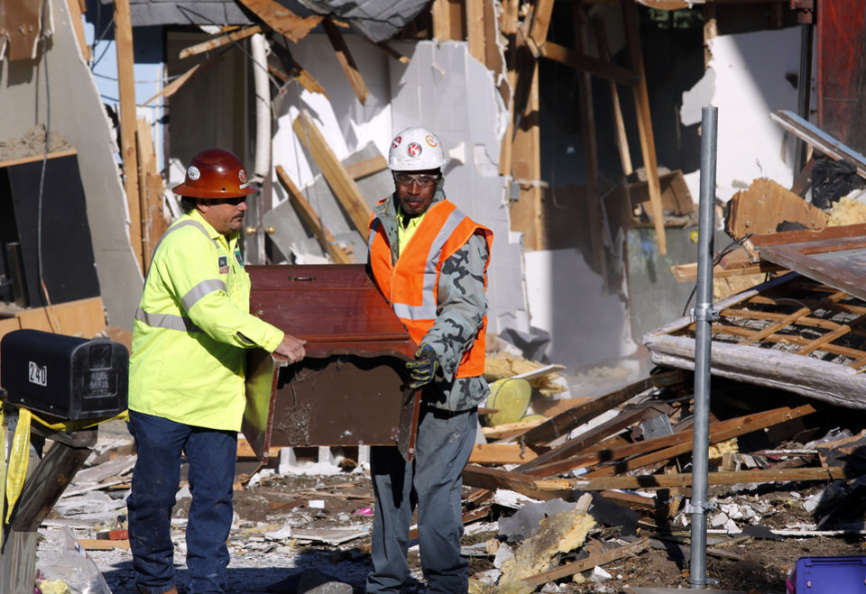 Demolition experts remove a piece of furniture from the home of Jeff Bush, 37, during demolition Monday, March 4, 2013 in Seffner, Fla.  A sinkhole opened up underneath the house late Thursday, Feb. 28, 2013, swallowing Jeff Bush, 37.  The 20-foot-wide opening of the sinkhole was almost covered by the house, and rescuers said there were no signs of life since the hole opened Thursday night.  (AP Photo/Scott Iskowitz)
