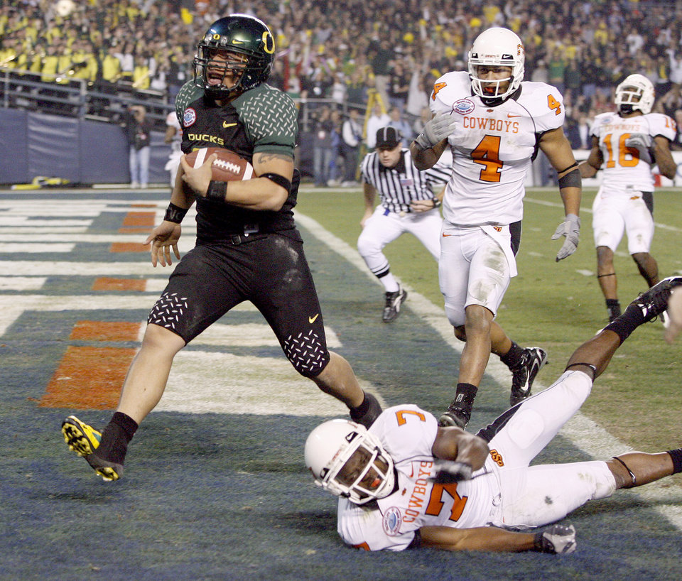 Photo - Oregon's Jeremiah Masoli runs past OSU's Maurice Gray, center, and Patrick Lavine for a touchdown during the Holiday Bowl college football between Oklahoma State and Oregon at Qualcomm Stadium in San Diego, Tuesday, Dec. 30, 2008.  PHOTO BY BRYAN TERRY, THE OKLAHOMAN.