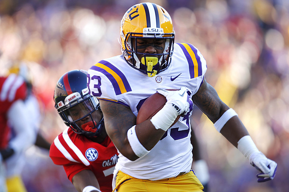 Photo - FILE - In this Nov. 17, 2012, file photo, LSU running back Jeremy Hill (33) rushes past Mississippi defensive back Trae Elston (7) on a 27-yard touchdown carry during the first half of their NCAA college football game in Baton Rouge,  Hill, already serving two years' probation in connection with a 2011 arrest, was arrested again early Saturday morning, April 27, 2013, after allegedly punching another man in the side of the head outside a Baton Rouge bar near campus. (AP Photo/Gerald Herbert)