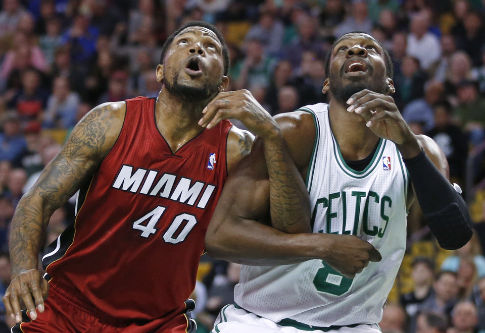 Photo - Miami Heat forward Udonis Haslem (40) and Boston Celtics forward Jeff Green (8) lock arms as they fight for position during a free throw in the first quarter of an NBA basketball game in Boston Wednesday, March 19, 2014. (AP Photo/Elise Amendola)