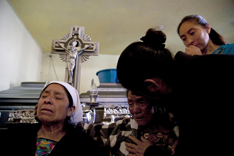 Relatives mourn during a funeral service for members of the Vasquez family who were buried alive when their house collapsed during an earthquake in San Cristobal Cucho, Guatemala, Thursday, Nov. 8, 2012. The family died when a magnitude 7.4 earthquake struck on Wednesday, collapsing their home and burying 10 members of their family, including a 4-year-old child, in the rubble. The powerful quake killed at least 52 people and left dozens more missing. (AP Photo/Moises Castillo) ORG XMIT: GUA113