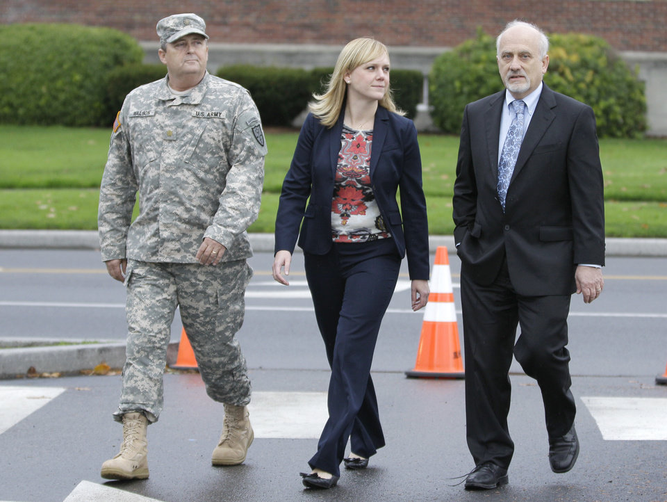 Photo -   Emma Scanlan, center, the civilian defense attorney for U.S. Army Staff Sgt. Robert Bales, walks Tuesday Nov. 13, 2012, with with Bales' military defense attorney, Maj. Gregory Malson, left, and attorney Lance Rosen, right, on Joint Base Lewis McChord in Washington state, where a preliminary hearing ended Tuesday for Bales, who is accused of 16 counts of premeditated murder and six counts of attempted murder for a pre-dawn attack on two villages in Kandahar Province in Afghanistan last March. (AP Photo/Ted S. Warren)