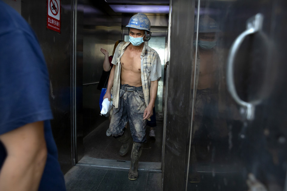 Photo -  A construction worker wearing a face mask to protect against the coronavirus walks out of an elevator in Beijing, Wednesday, July 29, 2020. China reported more than 100 new cases of COVID-19 on Wednesday as the country continues to battle an outbreak in Xinjiang. (AP Photo/Mark Schiefelbein)