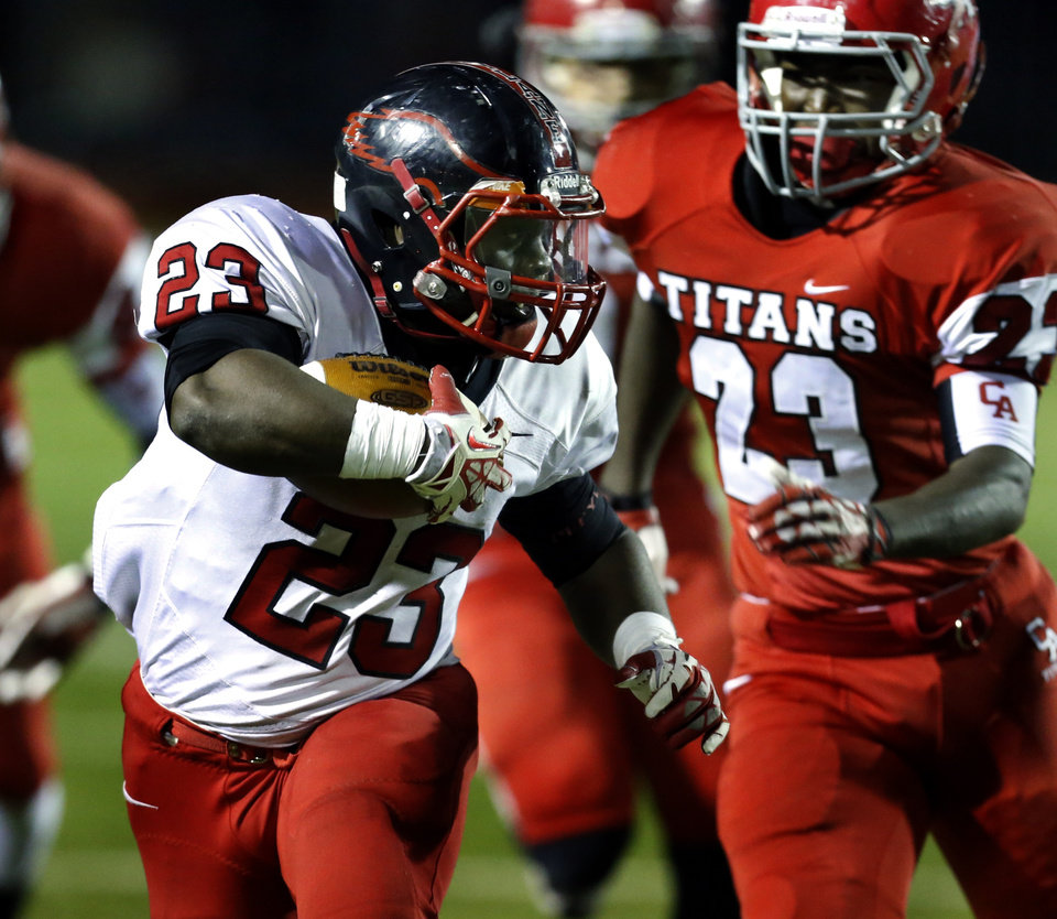 Photo - Del City's Anthony Mason carries pursued by by Carl Albert's Mike Mitchell as the Titans play the Del City Eagles on Friday, Nov. 15, 2013 in Midwest City, Okla. Photo by Steve Sisney, The Oklahoman