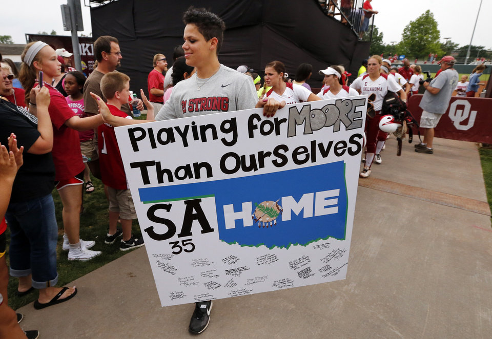 Photo - Sooner Jules Townsend carries a sign supporting Moore tornado victims and Sydney Angle after the NCAA Super Regional softball as the University of Oklahoma (OU) Sooners defeats Texas A&M 10-2 at Marita Hines Field on Friday, May 24, 2013 in Norman, Okla. Photo by Steve Sisney, The Oklahoman