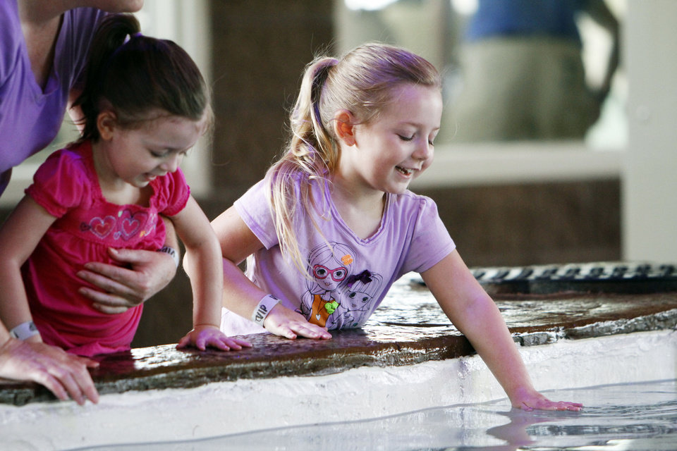 CHILD / CHILDREN / KIDS: From Left, Emily Ogle (3) and Morgan Ogle (5)  of Edmond lean over to pet a sting ray at the Oklahoma City Zoo's newest Sting Ray Bay exhibit on Tuesday, July 16, 2013. Photo by Aliki Dyer/ The Oklahoman