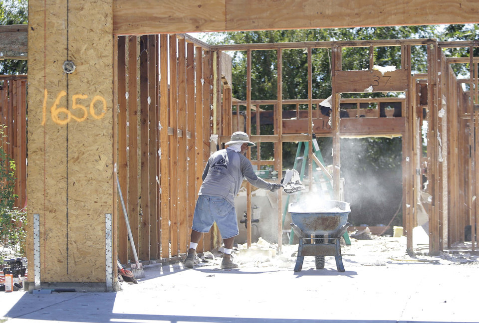 Photo - A worker clears debris from a home destroyed by a suspicious fire in Yuba City, Calif., Thursday, Aug. 29, 2013.  Sutter County District Attorney Carl Adams was one of several suitors of the homes's occupant, Sarah Garibay, 32, who said she had a brief affair with the district attorney.  Garibay told investigators he was one of three lovers who had recently expressed jealousy or anger toward her but she told the Marysville Appeal-Democrat that she does not believe he is in involved in the fire that destroyed the home in July. (AP Photo/Rich Pedroncelli)