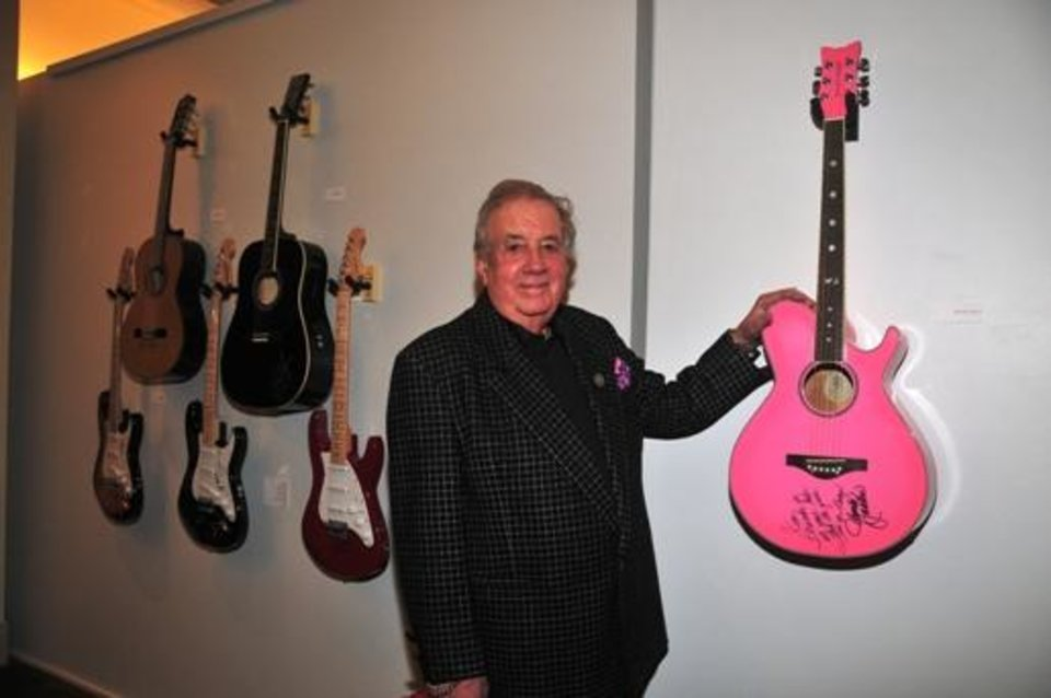 "Music impresario Jim Halsey poses with Wanda Jackson's guitar at the January opening event for the exhibit ""Starmaker: Jim Halsey and the Legends of Country Music"" at the Gaylord-Pickens Oklahoma Heritage Museum. the In the background from left are other signed guitars from Halsey's collection, including guitars from Aerosmith, Kenny Rogers, BB King, Bob Dylan and Carlos Santana."