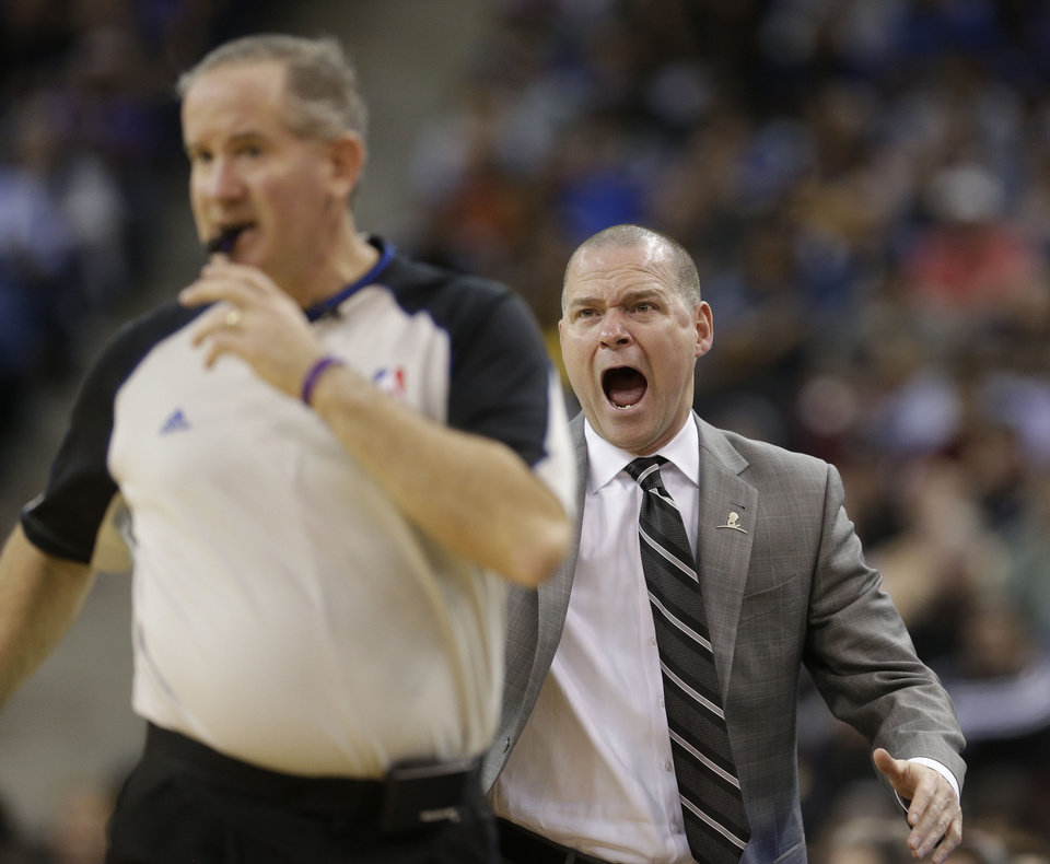 Photo - Sacramento Kings head coach Michael Malone, right, shouts at Official Scott Wall about a call during the fourth quarter of an NBA basketball game against12Golden State Warriors in Sacramento, Calif., Wednesday, Feb. 19, 2014. The Warriors won 101-92.(AP Photo/Rich Pedroncelli0