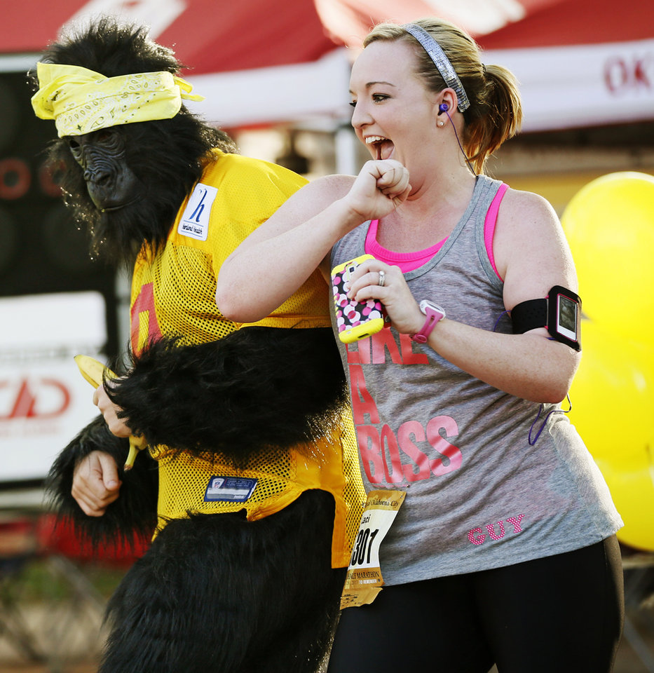 Photo - Runner Laci Dilibero takes a break from her race to dance with Reed Hammond in a gorilla costume on Gorilla Hill near NW 40th and Shartel Ave. during the Oklahoma City Memorial Marathon in Oklahoma City, Sunday, April 28, 2013. Photo by Nate Billings, The Oklahoman