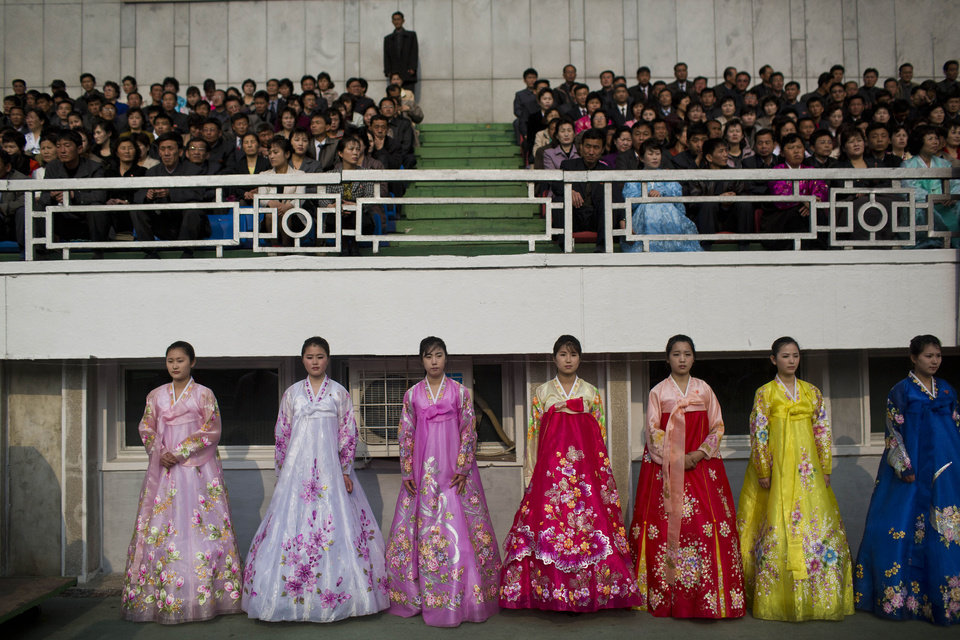 Photo - North Korean women in traditional dresses stand next to the running track inside Kim Il Sung Stadium during the running of the Mangyongdae Prize International Marathon in Pyongyang, North Korea on Sunday, April 13, 2014. The annual race, which includes a full marathon, a half marathon, and a 10-kilometer run, was open to foreign tourists for the first time this year. (AP Photo/David Guttenfelder)