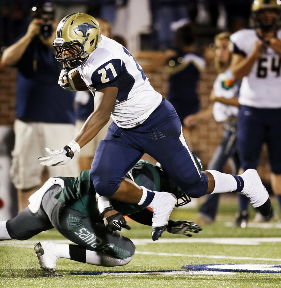 Photo - Southmoore's Karltrell Henderson (27) gets tripped up on a run during a high school football game between Edmond Santa Fe and Southmoore at Wantland Stadium in Edmond, Okla., Thursday, Sept. 20, 2012. Photo by Nate Billings, The Oklahoman