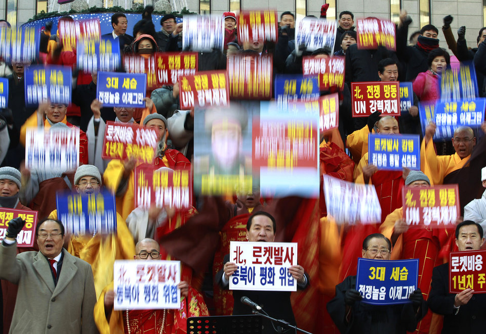 "South Korean religious leaders raise placards and shout slogans during a rally denouncing North Korea's rocket launch in Seoul, South Korea, Wednesday, Dec. 12, 2012. North Korea fired a long-range rocket Wednesday in its second launch under its new leader, South Korean officials said, defying warnings from the U.N. and Washington only days before South Korean presidential elections. The words read ""Denounce North Korea's rocket launch and overthrow family succession through three generations!"" (AP Photo/Ahn Young-joon) ORG XMIT: SEL112"
