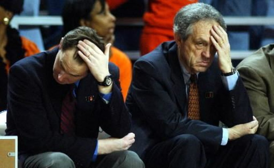 Photo - Oklahoma State assistant coach Sean Sutton, left, bows his head as his father and head coach Eddie Sutton takes a disgusted glance at the court in the second half of No. 9 Oklahoma State's 71-60 loss to Kansas State Saturday, Feb. 2, 2002, in Manhattan, Kan. AP Photo