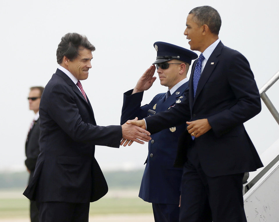 Photo - President Barack Obama, right, is greeted by Texas Gov. Rick Perry, left, during his arrival on Air Force One at Austin-Bergstrom International Airport, Thursday, May 9, 2013 in Austin, Texas. (AP Photo/Pablo Martinez Monsivais)