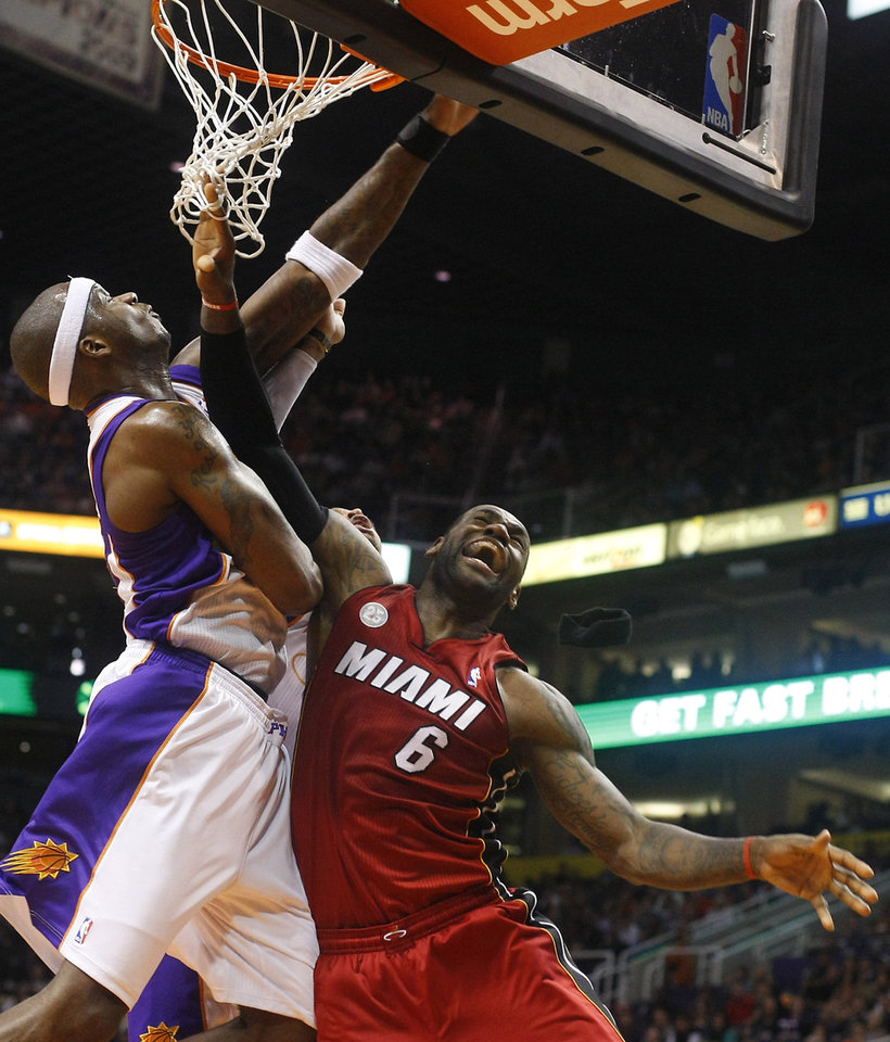 Miami Heat forward LeBron James (6) draws the foul and scores on Phoenix Suns center Jermaine O'Neal (20) in the second quarter during an NBA basketball game on Saturday, Nov. 17, 2012, in Phoenix. (AP Photos/Rick Scuteri)